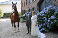Newlywed couple and horse with his in front of a house Stock Photo