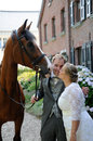 Newlywed couple and horse with his in front of a house Royalty Free Stock Photo