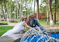 Newlywed couple kissing near fountain Stock Photography