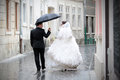 Newlywed couple in rain walking the urban streets with umbrella Royalty Free Stock Photo