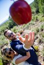 Newlyweds dressed elegantly try to catch a red apple like Adam and Eve.