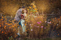 Newlyweds are embracing among the flowers in autumn park near wicker fence Stock Image