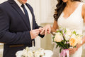Newlyweds exchange rings, groom puts the ring on the bride`s hand
