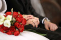 Newlyweds hands with wedding rings and red rose bouquet at the ceremony in church Royalty Free Stock Photos