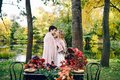 Newlyweds kissing under the plaid next to the festive table. Bride and groom in the park. Autumn wedding. Artwork Royalty Free Stock Photo