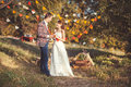 Newlyweds smile at each other standing in autumn park holding hands with a cup of coffee and smiling to Royalty Free Stock Photo