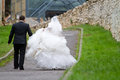 Newlyweds walking on the road seen from behind Stock Photo