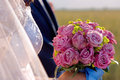 Newlyweds with wedding rose bouquet outdoors Stock Image