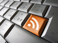 News rss feed symbol web and internet concept with icon and on a laptop computer key for blog and online business Royalty Free Stock Image