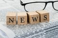 News text on wooden blocks with eyeglasses Royalty Free Stock Photo