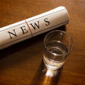 Newspaper and glass of water on desk Royalty Free Stock Image