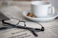Newspapers and coffee cup with reading glasses shallow depth of field focus on the word business Royalty Free Stock Images