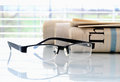 Daily newspapers rolled and black glasses in front of window Royalty Free Stock Image