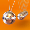 Newtons cradle against an orange background a colourful d rendered illustration Royalty Free Stock Photo