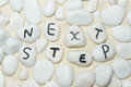 Next step words on pebbles Royalty Free Stock Photo