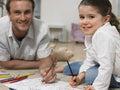 Niña con el hogar de coloring book at del padre Imagen de archivo