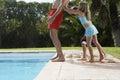 Niños que empujan al padre into swimming pool Imágenes de archivo libres de regalías
