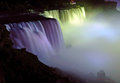 Niagara falls nighttime profile view a of the american side of the illuminated by multicolored floodlights from the canadian Stock Image