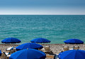 Nice beach with umbrellas blue near promenade des anglais in city of france Stock Photos
