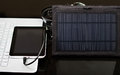 Nice black portable solar charger sitting on top of desk, tablet conected, white laptop, modern business technology Royalty Free Stock Photo