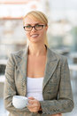 Nice businesswoman standing in the cafe take a break pleasant smiling charming holding cup and reveling drinking tea while Royalty Free Stock Photos
