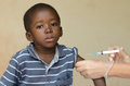 White doctor giving black African boy a needle injection as a vaccination Royalty Free Stock Photo