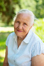 Nice elderly woman lovely sitting in a park sunny summer day Royalty Free Stock Photos