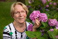 A nice elderly woman is posing in front of beautiful pink flowers Stock Photos