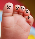 Nice foot of a baby with smiley faces painted toes Royalty Free Stock Photos