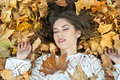 Nice girl covered with autumnal leaves young woman laying down on the ground covered by fall foliage in park beautiful sexy girl Stock Photography