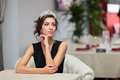 Nice girl in evening dress with a tiara on her head sits in a chair Stock Photos