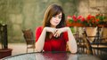A nice girl sits in a cafe red dress Stock Images