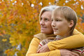 Nice grandmother with boy resting in the autumn park Royalty Free Stock Photos