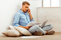Nice guy home young handsome man in the blue shirt and jeans talking smartphone using laptop sitting on cushions on the floor next Stock Images