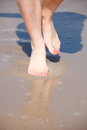 Nice legs in water pedicure red nail sand beach Stock Images