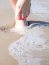 Nice legs in water pedicure red nail sand beach Stock Photo