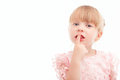 Nice little girl holding finger in front of mouth Royalty Free Stock Photo
