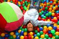 Nice little girl playing in the pool with colored plastic balls Royalty Free Stock Photo