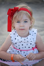 Nice little girl posing with sunglasses and a red ribbon baby wearing Royalty Free Stock Images
