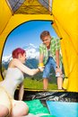 Nice morning in mountains man giving cup of tea to her girlfriend the tent on hiking trip Stock Photos