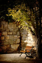 Nice old street angle bench tree and stone wall Royalty Free Stock Image