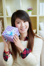 Nice present smiling young asian woman with a gift box at home Royalty Free Stock Photo