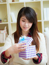 Nice present smiling young asian woman opening a gift box Stock Photo