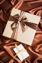 Nice present very gift box and greeting card on silk cloth with chocolate color Stock Photo