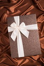 Nice present very gift box on silk cloth with chocolate color Royalty Free Stock Photo