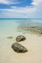 Nice rocks in the clear sea with blue sky  and white clouds in the background Royalty Free Stock Photo