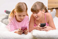 Nice sisters lying on settee modern children close up of cheerful content little girl holding mobile phones and while resting Royalty Free Stock Images