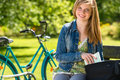 Nice student girl sitting in the park with bike Royalty Free Stock Photography