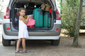 Nice thoughtful little girl with white dress loads the car for holidays Royalty Free Stock Photo