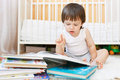 Nice toddler reading books against white bed Royalty Free Stock Photo